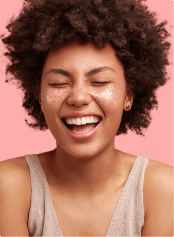 Woman with curly hair smiling with her eyes closed